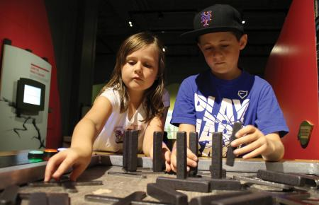 Children playing with the Build a Structure interactive in the Changing Earth exhibit at The Franklin Institute.