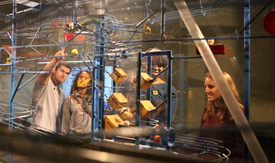 Guests watching the complex machine in the Sir Isaac's Loft exhibit at the Franklin Institute.