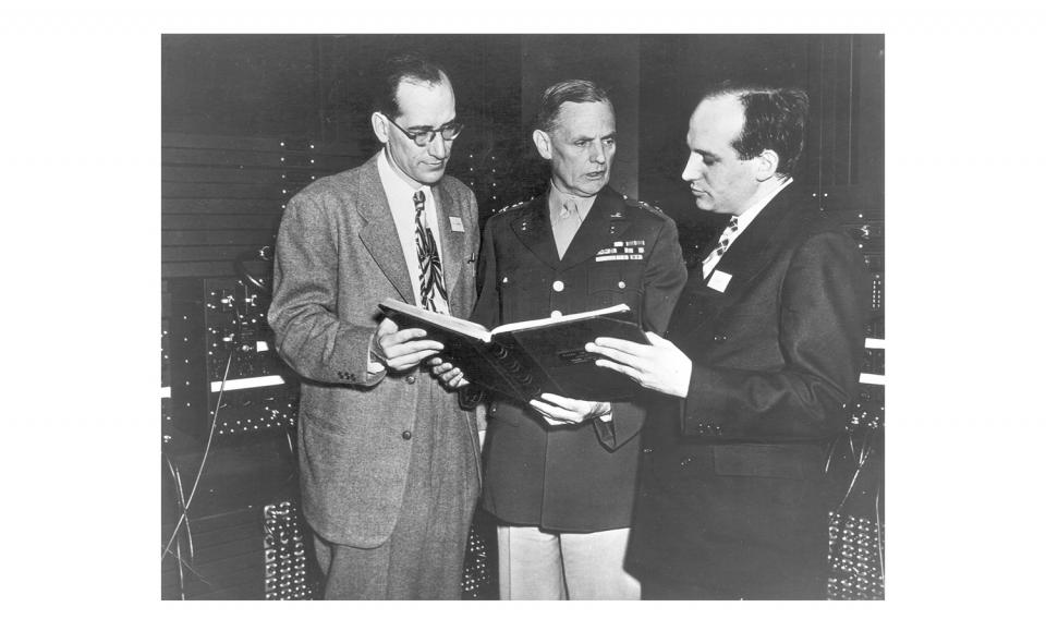 Black and white photo of John Mauchly And J Presper Eckert looking at an open book with a person in military uniform