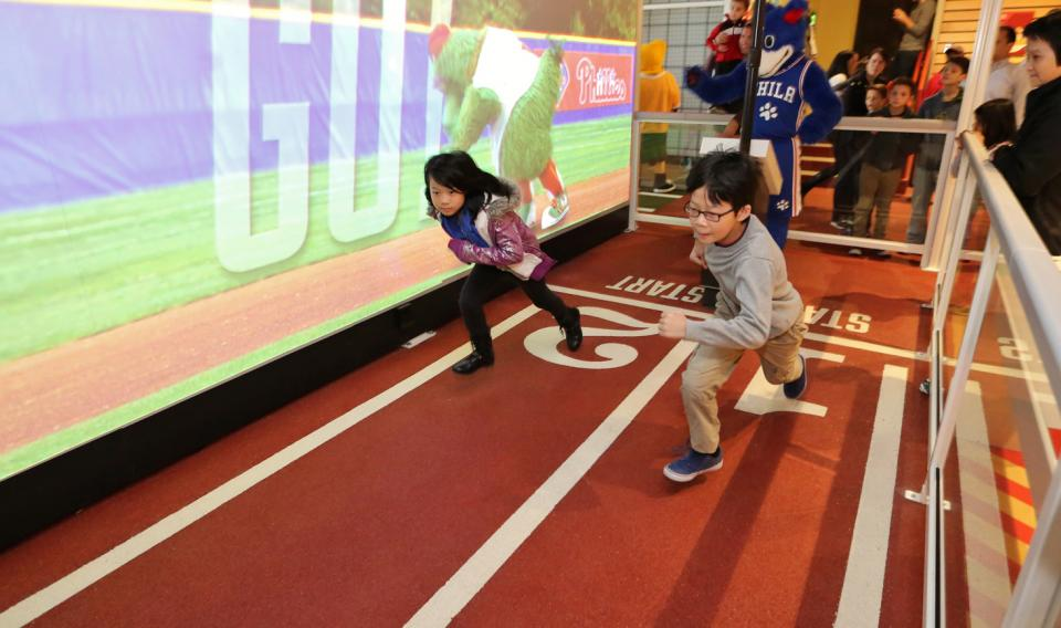 Two children racing the Phillie Phanatic in the SportsZone exhibit at the Franklin Institute.