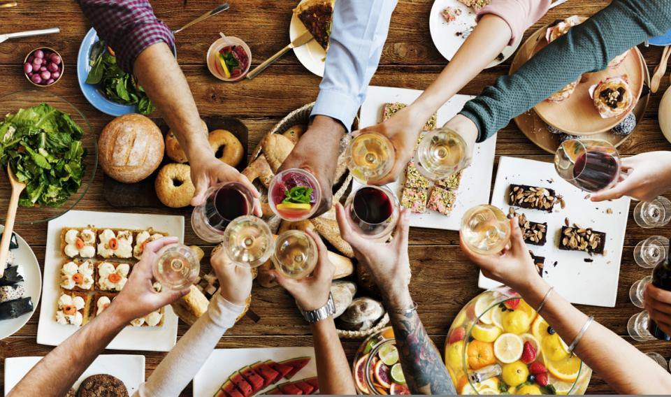 Overhead photo of friends having dinner and toasting glasses,