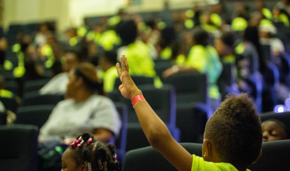 Child Raising Hand in Auditorium