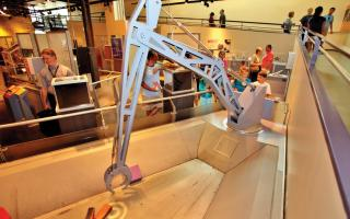Children operating a crane in the Amazing Machine exhibit at The Franklin Institute.
