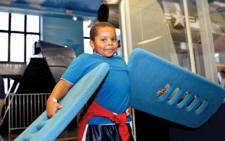 A boy using the foam wings interactive in the Franklin Airshow exhibit at The Franklin Institute.