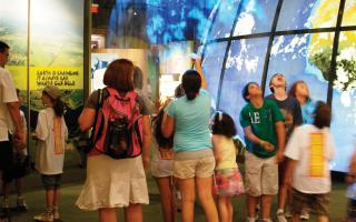 The Changing Earth exhibit entrance filled with visitors entranced by the vapor earth image.