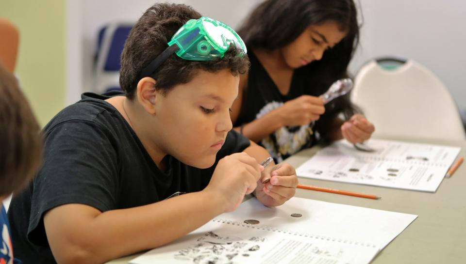 Elementary students sharpen their observational skills by using hand lenses to search for minute details on coins.
