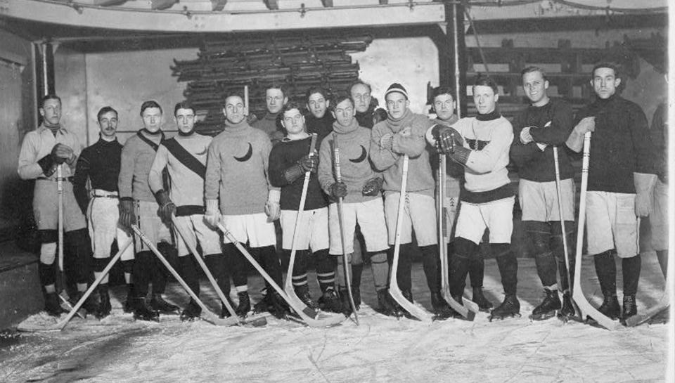 A hockey team posing together with their sticks.