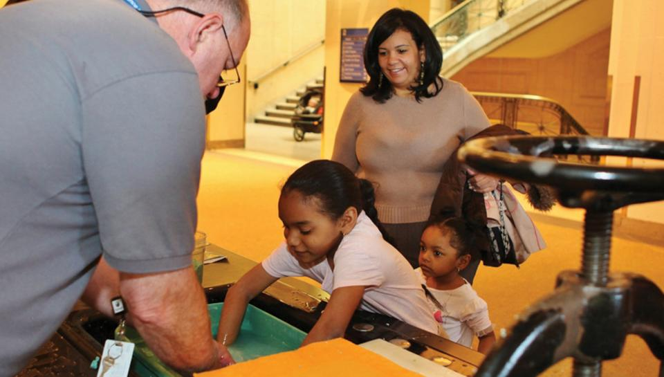 A family learns about papermaking at a live science demonstration cart.