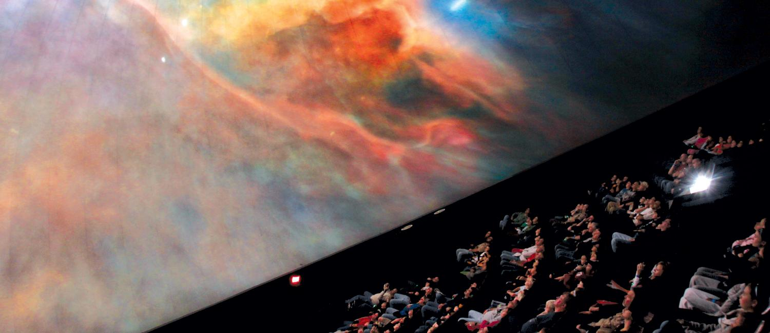 Visitors enjoying a movie about space in the IMAX theater.