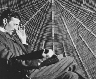 Black and white photograph of Nikola Tesla in front of the spiral coil of his high-voltage Tesla coil transformer