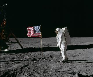 astronaut on moon with American Flag